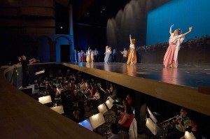 A view of the orchestra in the orchestra pit at Maumelle High School with dancers performing onstage