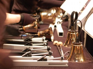 A photo of handbells and chimes on a long table