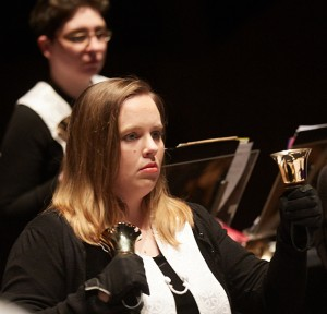 A photo of two women playing handbells
