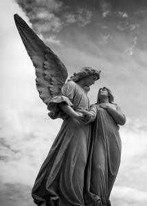 A cemetery statue of an angel leading a soul to heaven