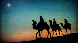Three kings follow a star on camel back, silhouetted against the sky at sunset